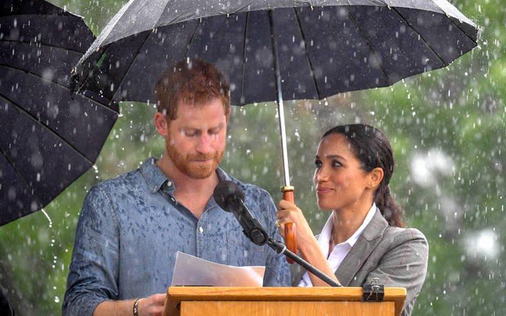 Η Μέγκαν Μαρκλ κρατά την ομπρέλα στον πρίγκιπα Χάρι για να μη βρέχεται